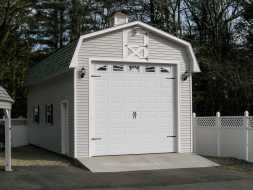 This personalized detached garage features, gambrel shingled roof, oversized garage door, & vinyl siding.