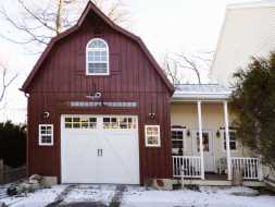 This custom built garage features barn style gambrel roof, red painted vertical siding, & lots of windows.