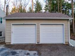 This detached 2 car garage includes vinyl shake siding, shingle roof, raised panel garage doors.