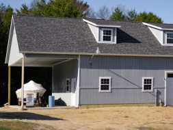 This awesome personalized garage features vertical painted siding, shingled roof with dormers, & lots of space.