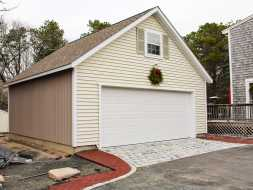 Detached garage with tan vinyl siding, storage area, & shingle roof.