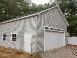 This large garage features high ceilings, very wide single garage door with transom window above, & electrical.