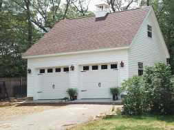 This beautiful 2 car garage features lots of windows, second story, cupola, & vinyl siding with shingle roof.