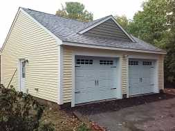 This custom 2 car garage features vinyl siding & shingle roof, with decorative dormer.