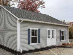 This detached garage has vinyl siding, shingled roof, large windows, & double door.