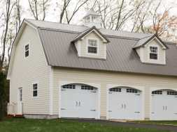 3 car garage features metal gambrel roof, carriage house garage doors, double dormers, cupola, Hardie board siding exterior.