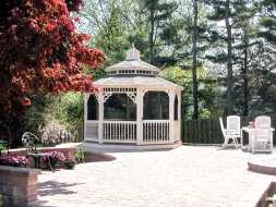 This patio gazebo features vinyl construction, screened, and a shingle roof.