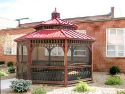 This wood gazebo features octagonal shape with a metal roof, and is screened.