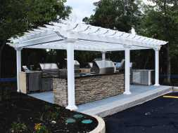 This white vinyl pergola completes this backyard kitchen area and is built with durable materials made to last a lifetime.