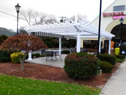 White vinyl commercial pergola, built on stone patio, plus features a ez-shade.
