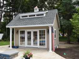 This poolhouse features full glass doors with side windows plus a dormer and cupola accent.