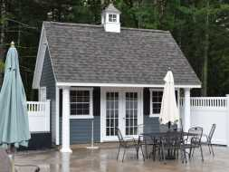 This A-frame style poolhouse has vinyl siding exterior with shingle roof plus has cupola accent.