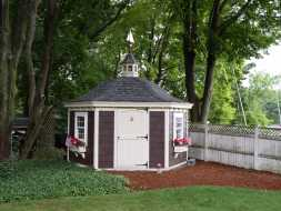 Hexagon shed with cupola accent curved shingle roof, and weathervane.