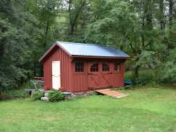 This is a red painted board & batten storage shed with blue metal roof.