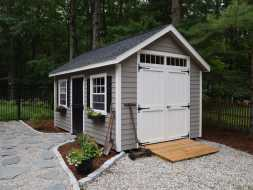 This storage shed has vinyl siding and shingled roof with double doors and equipment ramp