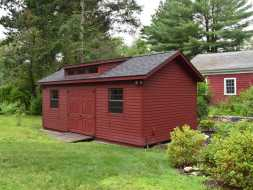 This red painted storage shed has a dormer added with double door & ramp