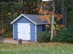 Storage Shed features vinyl siding & trim and shingled roof with double doors for equipment with a ramp