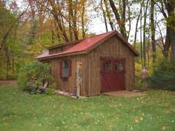 Storage shed featuring cedar board & batten siding with red doors and window shutters and a dormer roof.