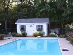 This backyard storage shed doubles as pool storage and has good looks with vinyl siding and window shutters.