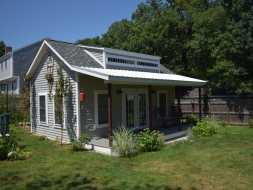 This shed features a porch front and dormer roof and is fully finished inside with electric.