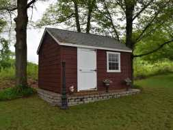 This backyard shed is personalized with paint of choice and all wood doors and is on a crushed stone base.