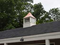 Vinyl cupola on commercial building with polished copper roof and widows.