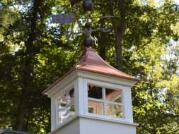 Shed cupola with copper roof and windows and weathervane.