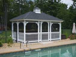 Rectangle vinyl gazebo featuring decorating spindles and fully screened with a cupola accent.