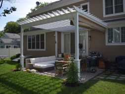 Pergola attached to house with outdoor furniture plus features a EZ shade.