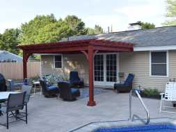 Outdoor wood pergola is stained to match customer preference, attached to the house.