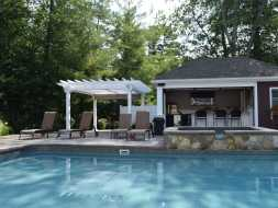 Pergola next to poolhouse bar is great addition to this backyard entertainment area.