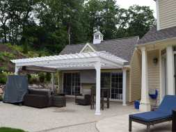 Custom attached pergola goes great in front of this poolhouse plus features a EZ shade.