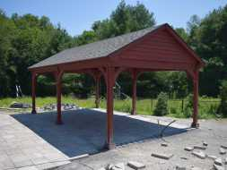 Custom pavilion featuring a gable roof design an stained wood construction with a shingle roof.