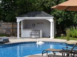 Pavilion with bar and privacy wall adds perfect addition to this backyard pool area.