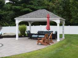 Vinyl poolside pavilion with hip shingle roof and vinyl columns is perfect addition to this backyard.