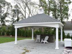 Large pavilion with rock front bar and stained T&G ceiling boards, plus vinyl columns, and features cupola accent.