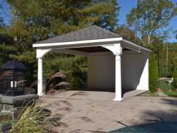 Backyard pavilion with privacy wall and electrical package, features vinyl columns and composite deck.