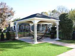 Custom pavilion with round decorative columns on rock patio and features hip roof design and stained wood ceiling.