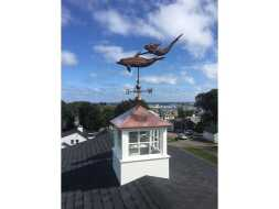 Vinyl cupola with copper hip roof and fixed glass windows with weathervane.