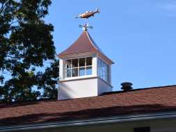 Vinyl cupola with shiny copper roof and fixed glass windows with a bass weathervane.
