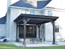 Large dark stained wood pergola on backyard patio over outdoor dining area.