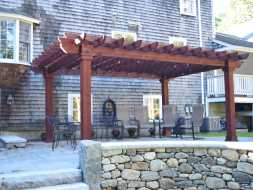 Red stained wood pergola on patio deck