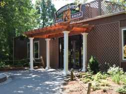 Commercial wood vinyl pergola over store entrance, features round vinyl columns and square cut wood beams.