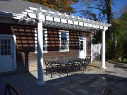 White vinyl attached to garage pergola, enhances the outdoor dining area.