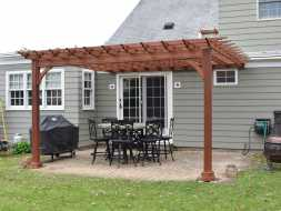 Stained cedar wood pergola attached to the house, adds value and style to any backyard.
