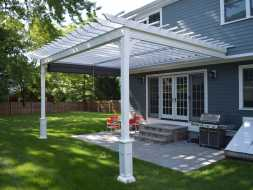 All vinyl constructed white pergola that is attached to the house over the back patio area.