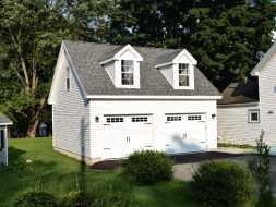 Custom 2 car garage featuring vinyl exterior siding, colonial dormers, and an upstairs loft.