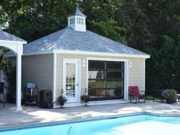 Pool house featuring a french door, glass design, hip roof, and a cupola.