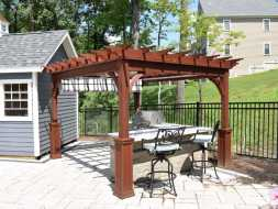 Wood stained pergola with a shade canopy over an outdoor kitchen