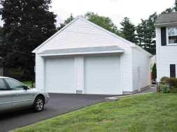 Custom 2 Car Garage featuring vinyl siding, A frame roof, and 2 bay doors.